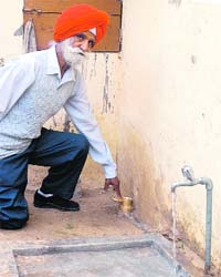 Balbir Singh, a resident of Railon Khurd village in Ropar district, points to the water meter installed in a house